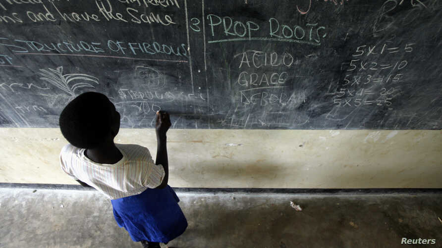 Grace Debroha, a 13-year-old orphan, writes the names of body parts on a chalkboard at St. Jude's Orphanage, outside Gulu, Uganda, June 10, 2007.