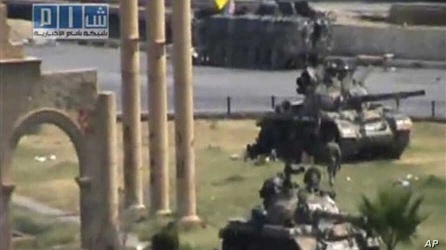 In this image made from amateur video released by the so-called Shams News Network, a loosely organized anti-Assad group and accessed via The Associated Press Television News on Aug. 1, 2011, military armored vehicles are seen in the central city of