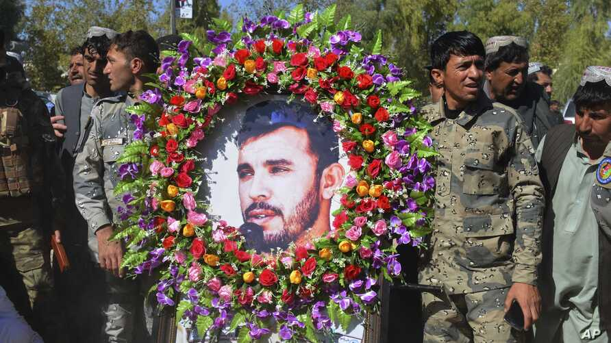 Military personnel held a photo of Gen. Abdul Raziq, Kandahar police chief, who was killed by a guard, during his burial ceremony in Kandahar, Afghanistan, Oct. 19, 2018.