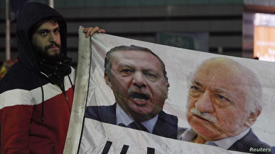 A demonstrator hold pictures of Turkey's Prime Minister Tayyip Erdogan and Turkish cleric Fethullah Gulen (R), during a protest against Turkey's ruling AK Party (AKP), demanding the resignation of Erdogan, in Istanbul December 30, 2013. Erdogan swore