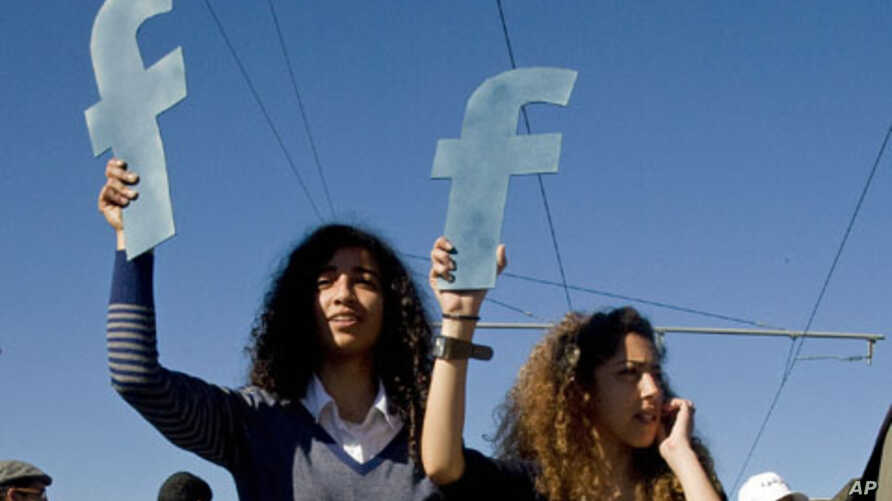 """Protesters hold """"f""""s in recognition of social network site Facebook's role in the North African revolts, during a protest by thousands over civil rights, in Rabat, Morocco,  March 2011."""