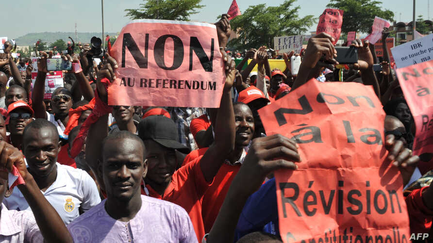 "FILE - Protestors carry a sign reading ""No to the referendum"" and ""No to Constitutional revision"" during a demonstration against a referendum on a constitutional revision on July 1, 2017, in Bamako."