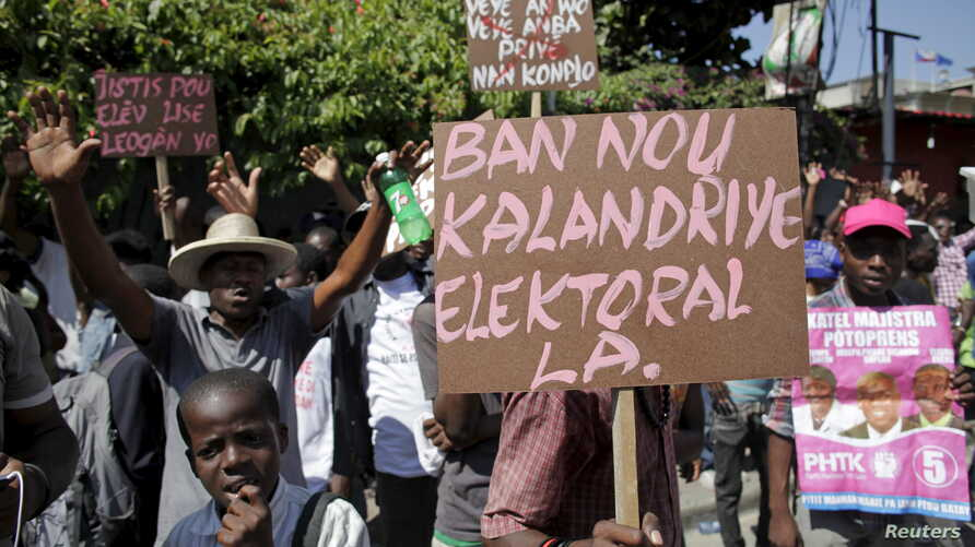 FILE - Supporters of PHTK political party hold signs during a demonstration to demand the organization of a postponed presidential runoff election in Port-au-Prince, Haiti, April 14, 2016.