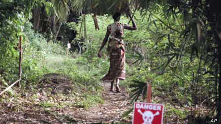 Woman enters forest area in Orientale Province in the DRC. The path has been cleared of landmines.
