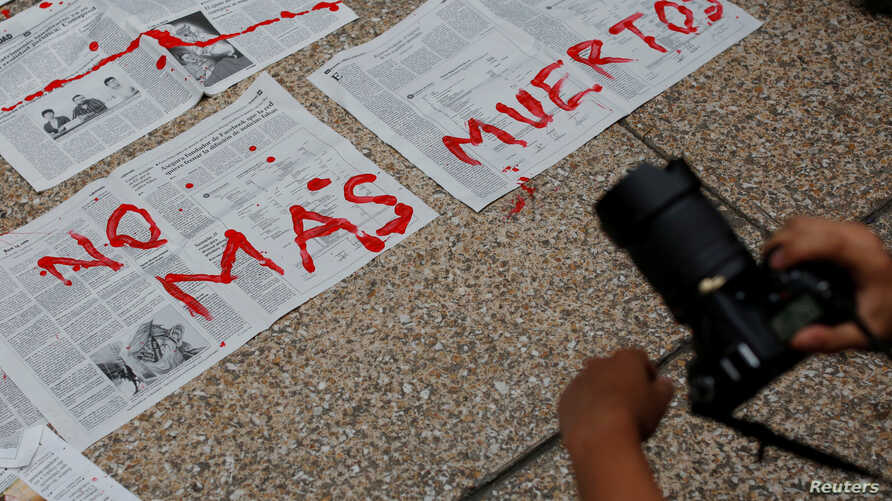 Journalists and activist paint on news papers with fake blood during a protest against the murder of the Mexican journalist Miroslava Breach, outside the Attorney General's Office (PGR) in Mexico City, Mexico, March 25, 2017.
