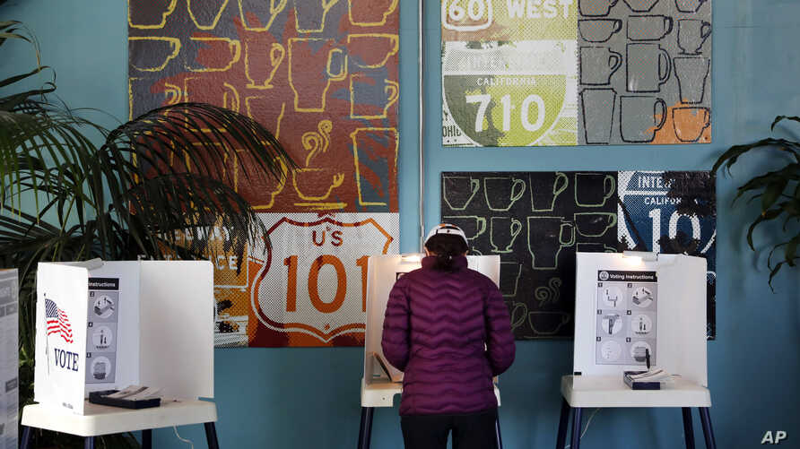 FILE - A woman votes at a polling station inside a coffee shop in Los Angeles, March 7,2017. The California secretary of state has again rejected a request for voter information from President Donald Trump's commission investigating alleged voter fra