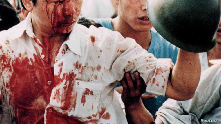 A blood-covered protester holds a Chinese soldier's helmet following violent clashes with military forces during pro-democracy demonstrations in Beijing's Tiananmen Square, June 4, 1989.