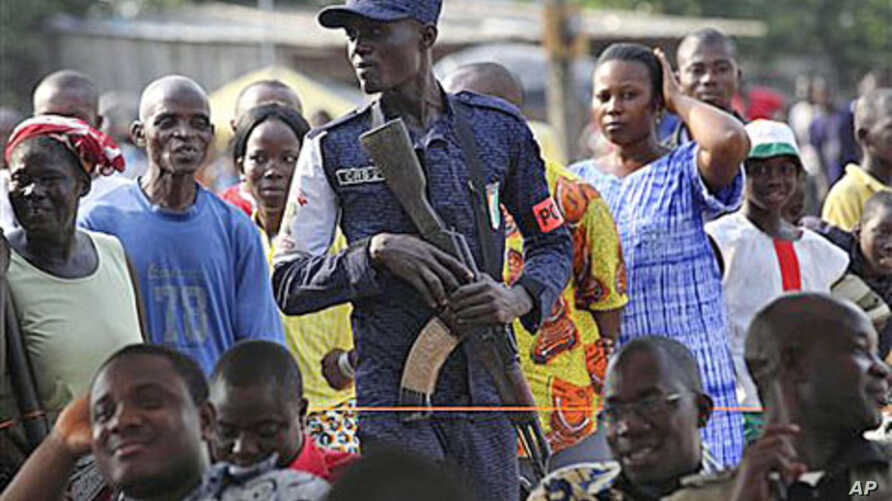 An Ivory Coast policeman stands guard during a youth rally in Abidjan, Ivory Coast, Dec 20, 2010