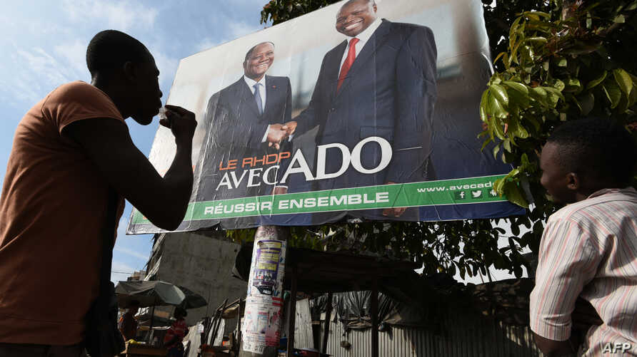 Campaign poster presenting the candidates of the Rally of Houphouetists for Democracy and Peace (RHDP) Ivorian President Alassane Ouattara (ADO) (R) and Albert Toikeusse Mabri of the UDPCI, in Kumasi, a popular district of Abidjan, Oct. 9, 2015.