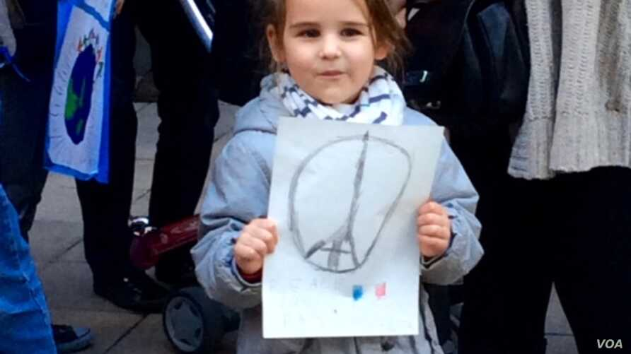 A girl holds a 'Peace for Paris' symbol, created by graphi
