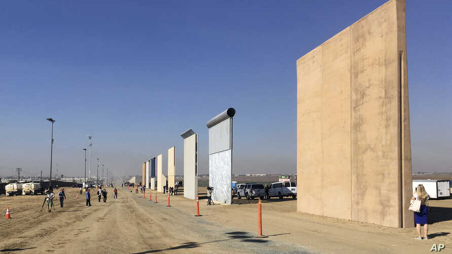 People look at prototypes of a border wall, Oct. 26, 2017, in San Diego. Contractors have completed eight prototypes of President Donald Trump's proposed border wall with Mexico, triggering a period of rigorous testing to determine if they can repel