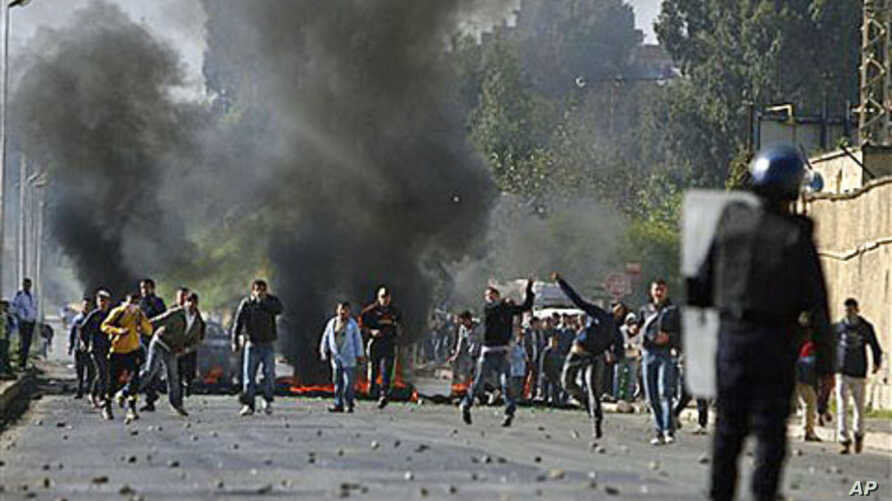 Youths clash with police officers in the El Harrache district of Algiers after prices were increased on basic food staples, Jan 6, 2011
