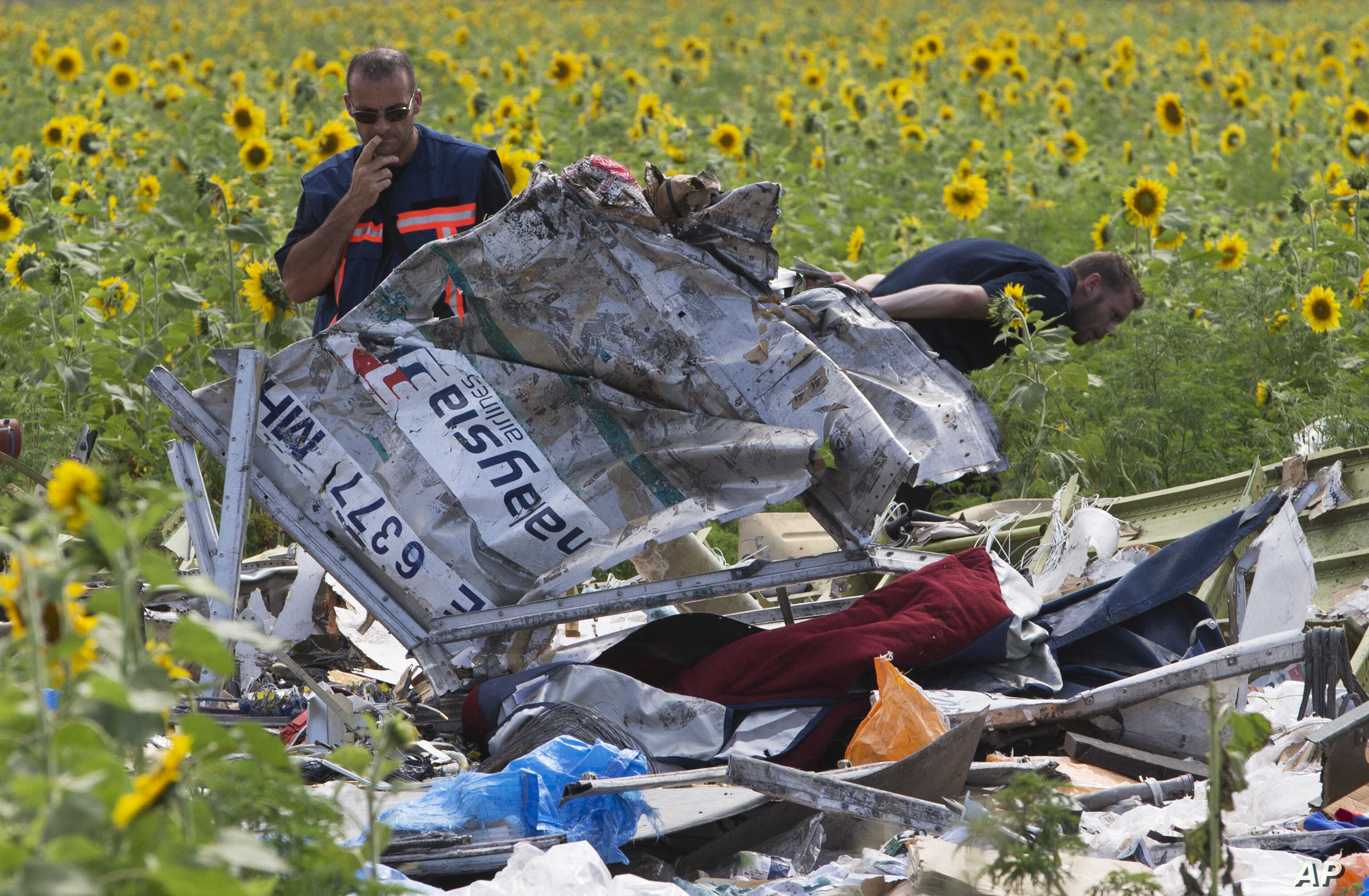 Dutch investigators examine pieces of the crashed Malaysia Airlines Flight 17 in the village of Rassipne, Donetsk region, eastern Ukraine, July 25, 2014.