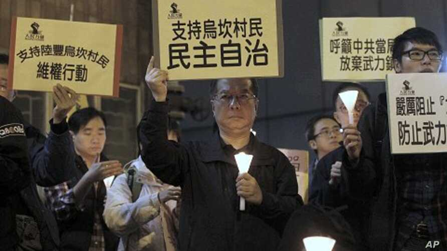 A protester, center, holds up a placard reading: 'Supporting Wukan villagers, democracy autonomy' during a candlelight vigil outside the China Liaison Office in Hong Kong to support the Wukan villagers, December 20, 2011.