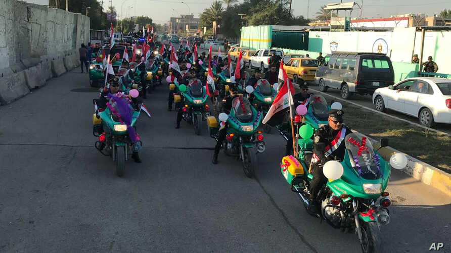 Iraqi security forces parade on motorcycles with national flags marking the one-year anniversary of the defeat of the Islamic State group in Iraq, in Tahrir Square, central Baghdad, Dec. 10, 2018.