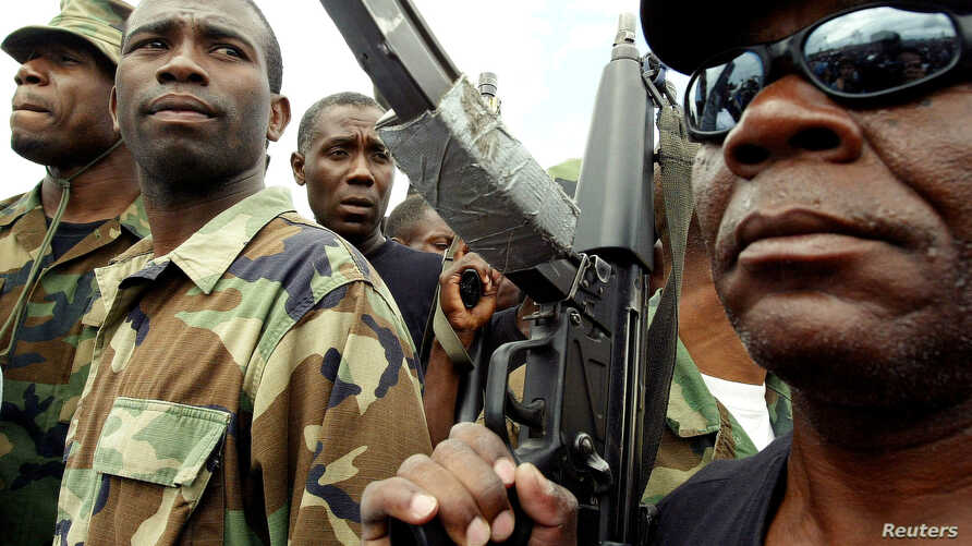 FILE - Guy Philippe, former police chief police, participates in a march into the city of Gonaives, Haiti, Feb. 19, 2004.