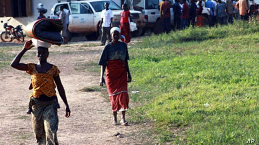 Ivorian refugees walk in the village of Loguatuo in Liberia