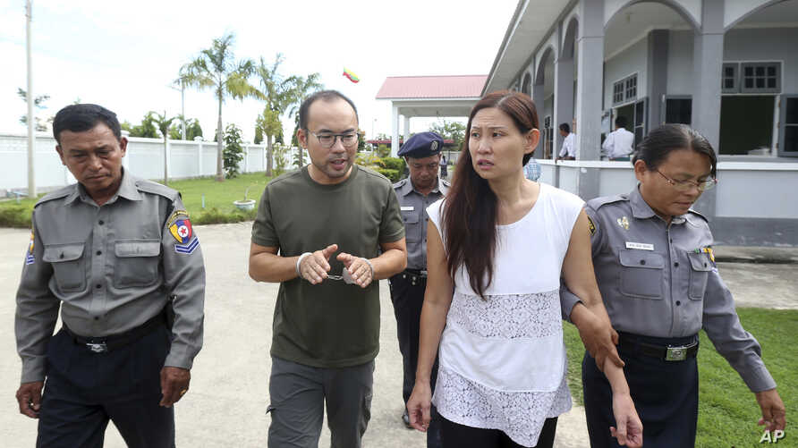 FILE - Singaporean journalist Lau Hon Meng, center left, and Malaysian journalist Mok Choy Lin, both accused of flying drones illegally over parliament buildings, are escorted during their trial at a court in Naypyitaw, Myanmar, Nov. 10, 2017.