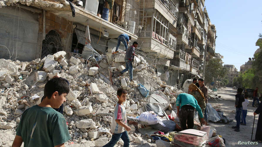 People remove belongings from a damaged site after an air strike Sunday in the rebel-held besieged al-Qaterji neighbourhood of Aleppo, Syria, Oct. 17, 2016.