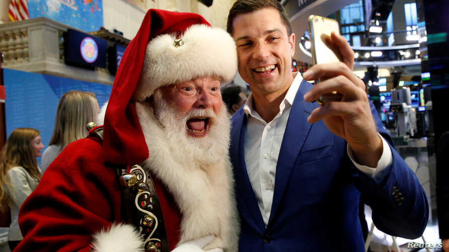 Tom Farley, president of the NYSE Group, poses for a selfie with Santa Claus, who rang the opening bell to celebrate the Macy's 90th Annual Thanksgiving Day Parade, at the New York Stock Exchange in New York City, Nov. 23, 2016.