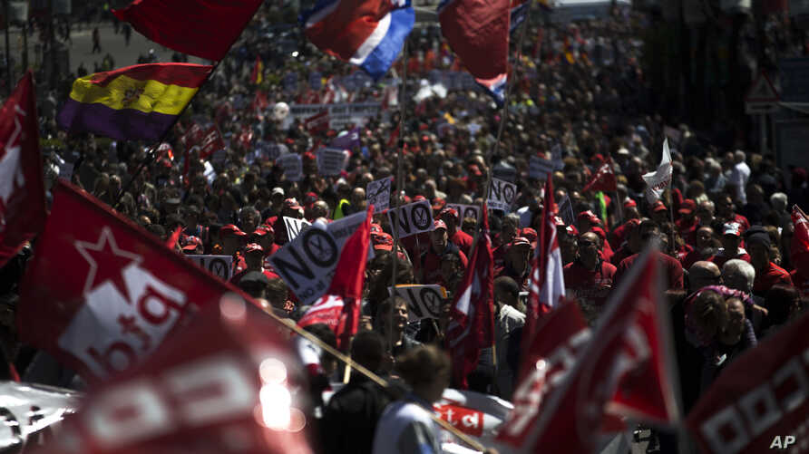People shout slogans and wave flags during a May Day workers march in Madrid, May 1, 2016. Trade unions and other groups staged rallies around the world Sunday to mark the International Workers Day.