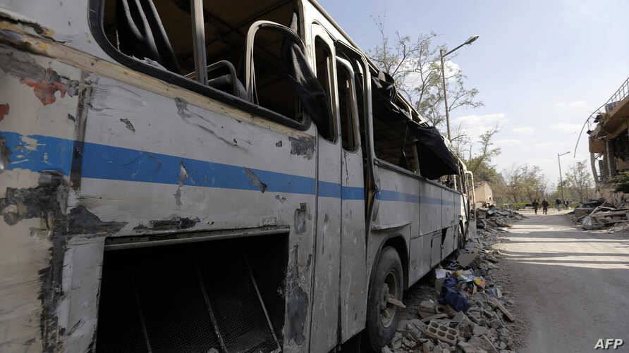 This picture taken on April 14, 2018 shows a destroyed bus near the wreckage of a building described as part of the Scientific Studies and Research Centre (SSRC) compound in the Barzeh district, north of Damascus, Syria