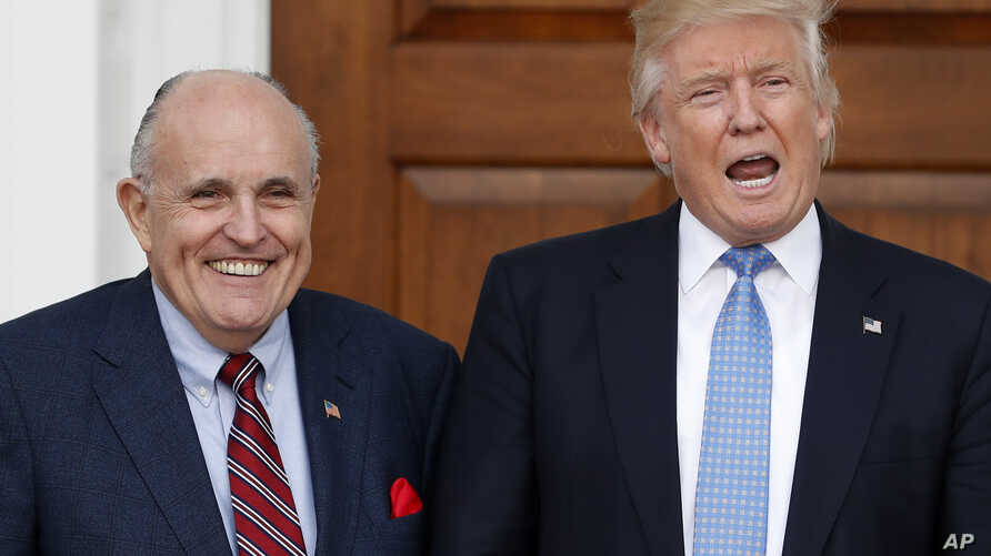 President-elect Donald Trump calls out to media as he and former New York Mayor Rudy Giuliani pose for photographs as Giuliani arrives at the Trump National Golf Club Bedminster clubhouse, Nov. 20, 2016, in Bedminster, N.J.