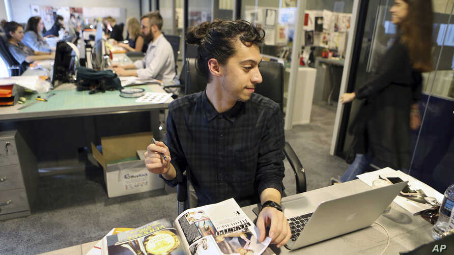 Mohammad Hazem Rezq, one of the Vogue staff works behind his desk at the magazine office at the Dubai Design District in Dubai, United Arab Emirates, Wednesday, March 15, 2017.