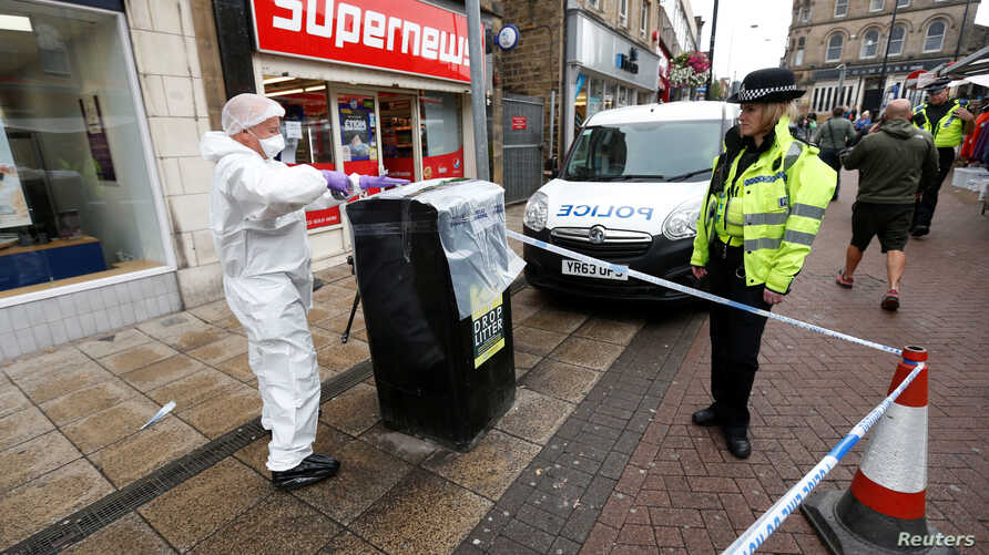 Police officers secure an area in the town center after reports of a stabbing in Barnsley, England, Sept. 8, 2018.