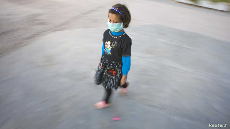 FILE - An Afghan girl wears a protective mask as she walks out of a school in Herat province, Nov. 3, 2009.