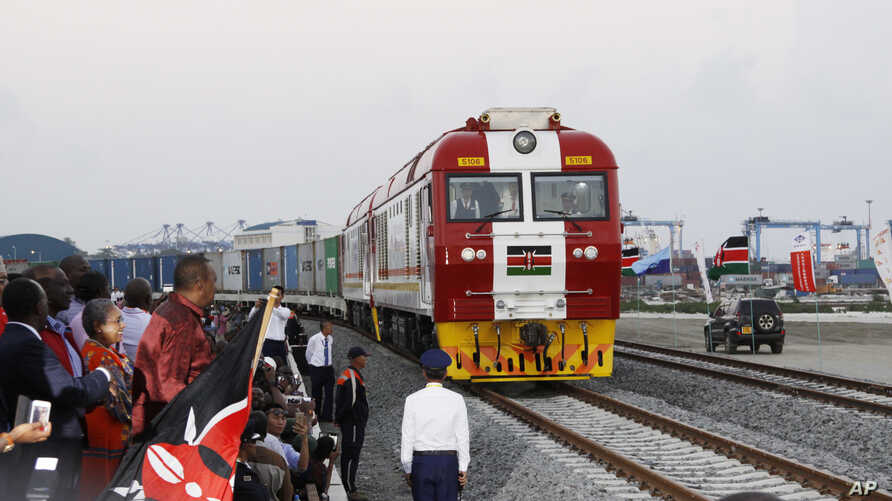 Kenyan President Uhuru Kenyatta, third from left, watches a cargo train carrying port containers begin its opening run from Mombasa to Nairobi, Kenya, May 30, 2017.