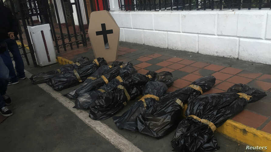 Dummies simulating corpses and a cardboard coffin are seen at the gates of the Venezuelan National Guard headquarters during a protest by opposition lawmakers in Caracas, Venezuela, June 20, 2017.