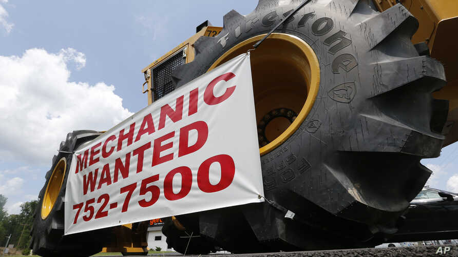 FILE - A help wanted sign is posted at a tractor dealership in Ashland, Va., June 9, 2015.