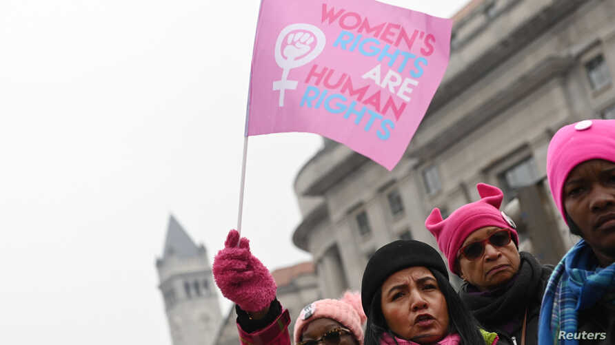 "Irene Olmos of Silver Spring, Md., waves a ""Women's Rights Are Human Rights"" flag as she participates in the third annual Women's March at Freedom Plaza in Washington, Jan. 19, 2019."