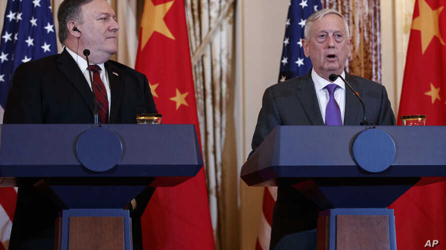 Secretary of State Mike Pompeo looks to Secretary of Defense Jim Mattis during a news conference with Chinese officials at the State Department in Washington, Nov. 9, 2018.