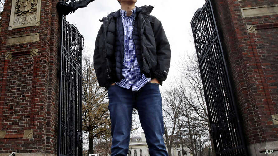 Harvard University graduate Jin K. Park, who holds a degree in molecular and cellular biology, poses at a gate at Harvard Yard in Cambridge, Mass., Thursday, Dec. 13, 2018. (AP Photo/Charles Krupa)