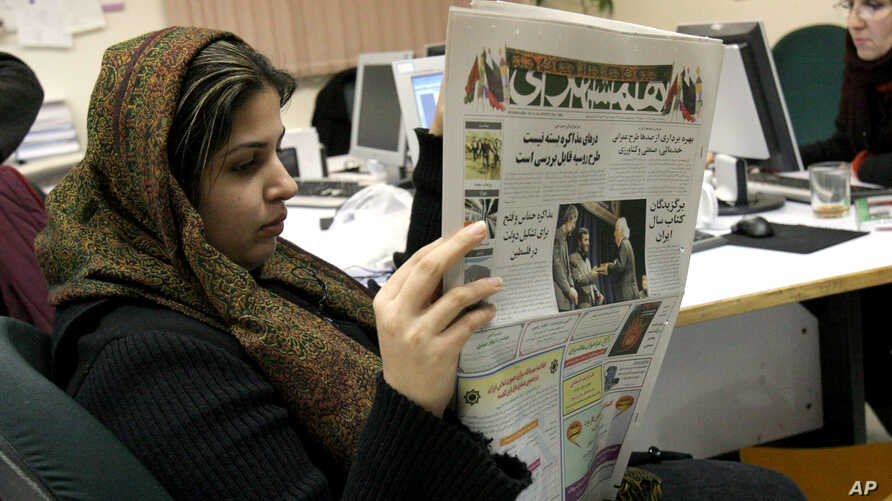 FILE - Iranian journalist Elahe Khosravi, reads Iranian daily newspaper Hamshahri, in Tehran, Iran on Tuesday, Feb. 7, 2006. The prominent Iranian newspaper said Tuesday it would hold a competition for cartoons on the Holocaust to test whether the We