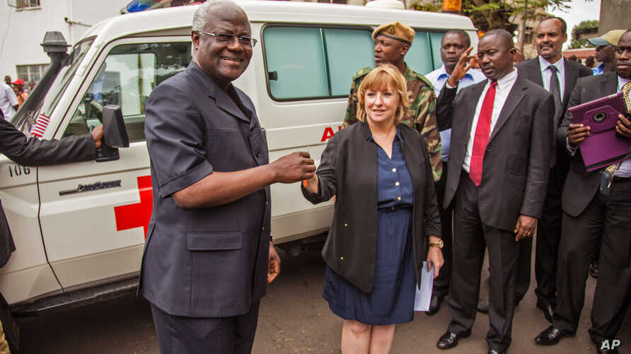 Sierra Leone's president Ernest Bai Koroma, left, is handed the keys to an ambulance by U.S. Embassy representative Kathleen FitzGibbon, center, one of five ambulances donated by the U.S. to help combat the Ebola virus in the city of Freetown, Sierra