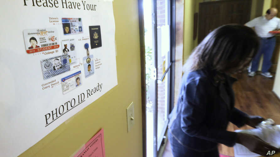 FILE - An election worker walks past a voter ID sign at a polling place in Little Rock, Arkansas, May 20, 2014.