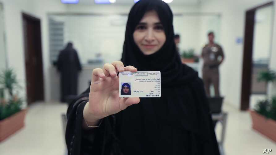 This image released by the Saudi Information Ministry shows Tahani Aldosemani, assistant professor at Prince Sattam Bin Abdulaziz University in Al-Kharj, as she displays her new driving license at the General Department of Traffic in the capital, Riy