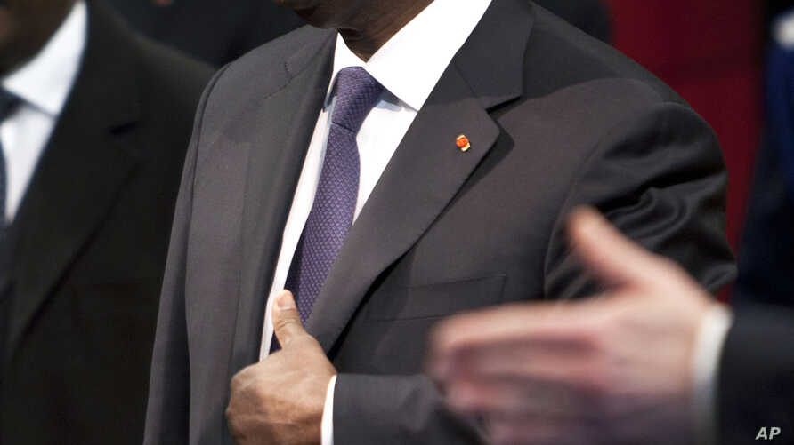 FILE - Ivory Coast President Alassane Dramane Ouatarra adjusts his jacket prior to deliver a speech at the Paris' city hall, in Paris, Friday Jan. 27,