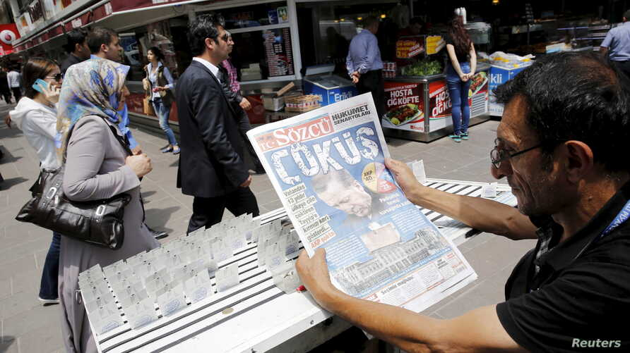 """A lottery ticket vendor reads a Turkish newspaper published with an headline reads """"downfall"""" and a portrait of Turkey's President Tayyip Erdogan in Ankara, Turkey, June 8, 2015. Erdogan will meet Prime Minister Ahmet Davutoglu on Monday to discuss S"""