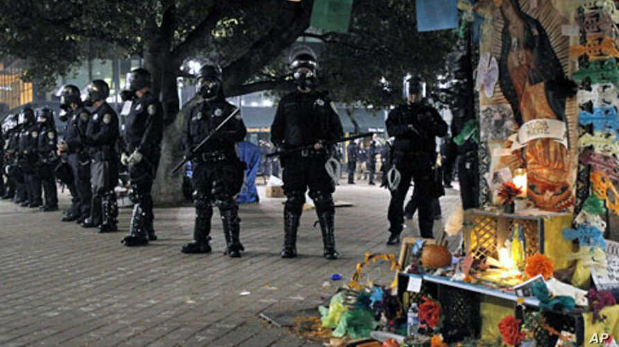 Police officers in riot gear form a line near a Day of the Dead shrine at the Occupy Oakland demonstration in Oakland, California, November 3, 2011