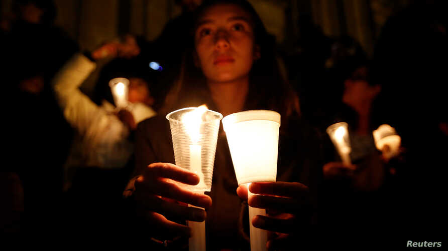"A supporter of the peace deal signed between the government and the Revolutionary Armed Forces of Colombia (FARC) rebels holds candles while attending a gathering at Bolivar Square during a ""Silent March"" in Bogota, Colombia, Oct. 5, 2016."