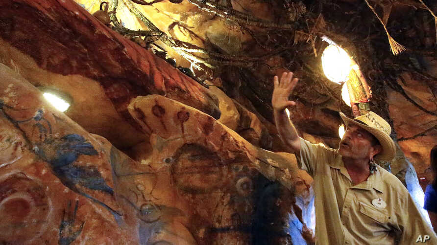In this April 29, 2017 photo, Joe Rohde, design and production leader for Pandora-World of Avatar land attraction, explains about the caverns and the meaning of the cave drawings of the Na'vi, the native inhabitants of the planet Pandora at Disney's