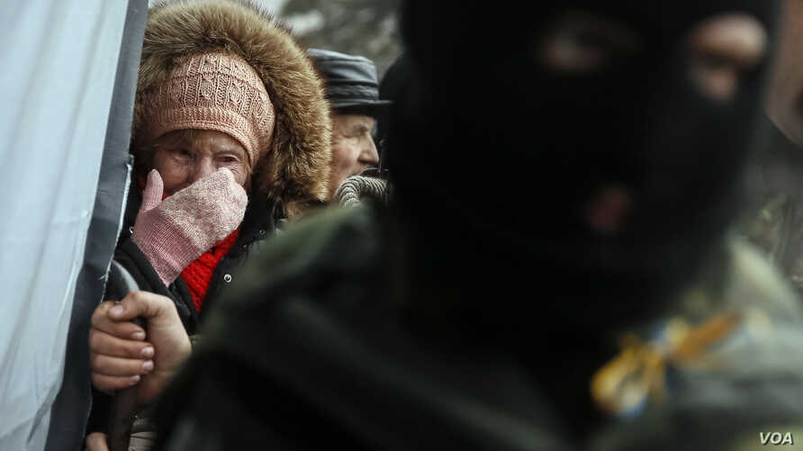 A woman cries as she waits for humanitarian aid near a Ukrainian serviceman stands nearby in Debaltseve, eastern Ukraine, February 6, 2015. Convoys of buses converged from two sides on the town of Debaltseve in eastern Ukraine on Friday after separat