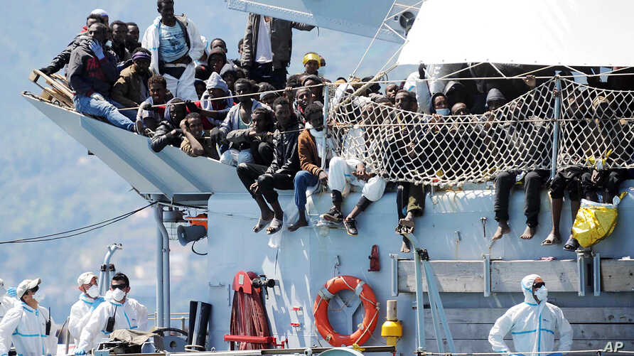 "Migrants wait to disembark from the Italian Navy vessel ""Chimera"" in the harbor of Salerno, Italy, April 22, 2015. Italy pressed the European Union on Wednesday to devise concrete steps to stop the deadly tide of migrants on smugglers' boats in the M"