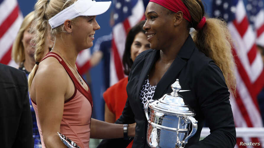 Serena Williams of the U.S. (R) and Caroline Wozniacki of Denmark chat as they hold their trophies following the women's singles finals match at the 2014 U.S. Open tennis tournament in New York, September 7, 2014.