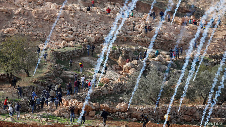 Tear gas canisters are fired by Israeli troops towards Palestinians during a protest against Israeli land seizures for Jewish settlements, near Ramallah in the occupied West Bank, Nov. 30, 2018.