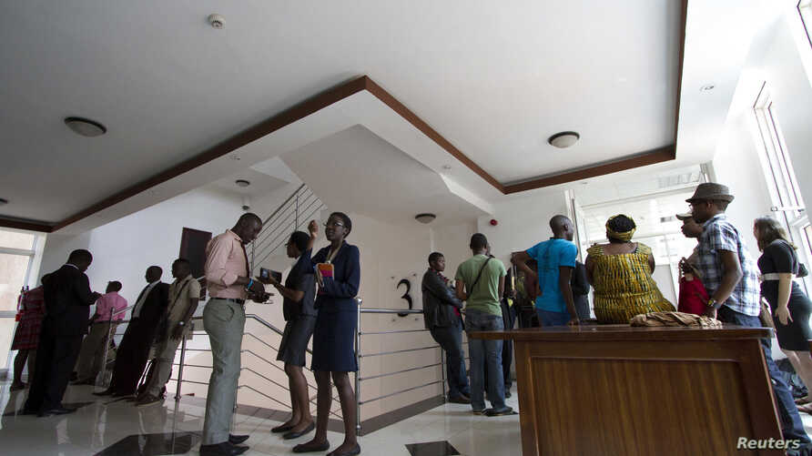 FILE - Gay and human rights activists wait outside the courts before filing a constitutional petition against a new anti-homosexuality law, in Uganda's capital Kampala, March 11, 2014.